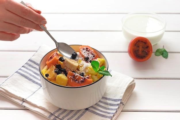 Kom verse fruitsalade, met gesneden tamarillo en yoghurt op de achtergrond
