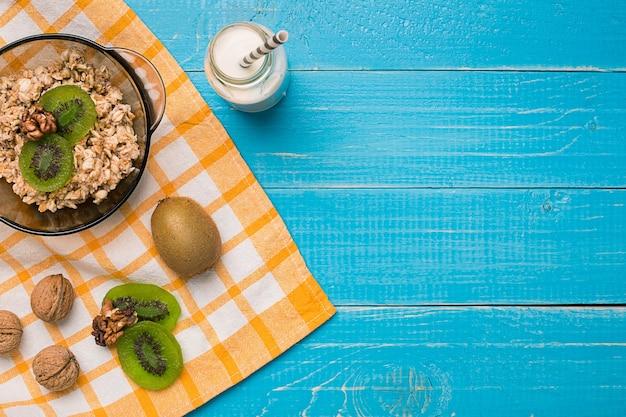 Kom verse havermoutpap met kiwi en noten op groenblauw rustieke tafel, warm en gezond eten voor het ontbijt. bovenaanzicht. ruimte kopiëren