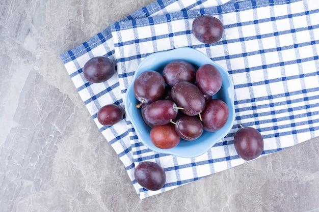 Kom verse pruimen op stenen achtergrond met tafellaken.