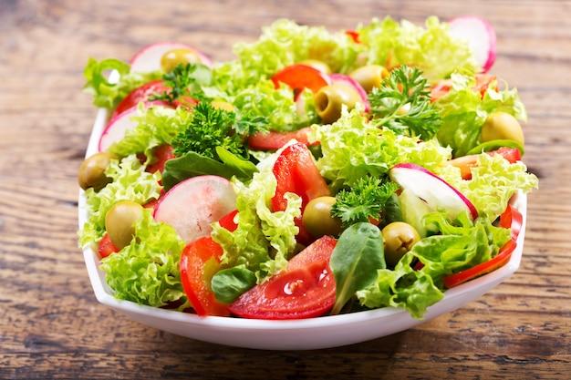 Kom verse salade met groenten en greens op houten tafel