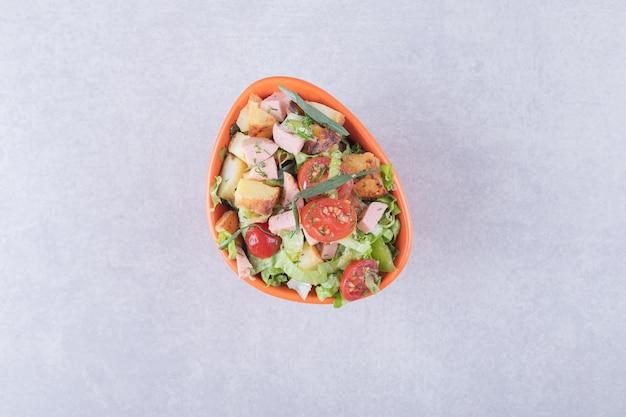 Kom verse salade met worstjes op marmeren achtergrond.