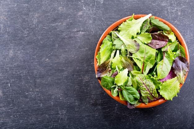 Kom verse salade op donkere, bovenaanzicht met kopie ruimte