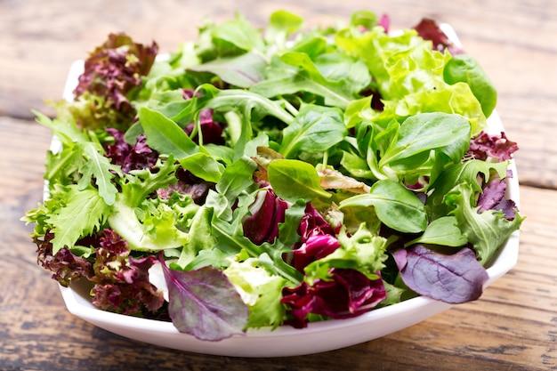 Kom verse salade op een houten tafel