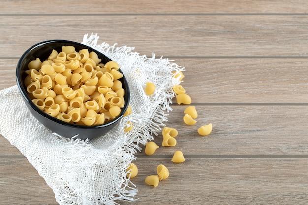 Kom vol met droge pasta op houten tafel.