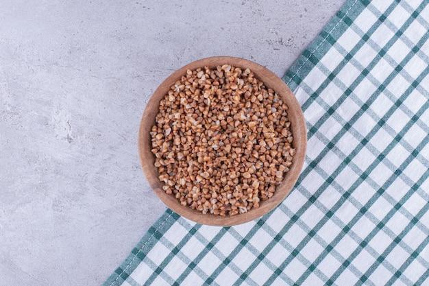 Kom vol smaakvol gekookt boekweit op een handdoek op marmeren achtergrond. hoge kwaliteit foto