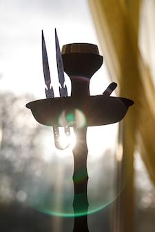 Kom waterpijp in stralen van de ondergaande zon op de achtergrond. met waterpijp rook. hete kolen op waterpijp cup