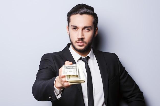 Kom werken en ontvang je eerste salaris. close-up van een jonge man in formalwear die geld uitrekt terwijl hij tegen een grijze achtergrond staat