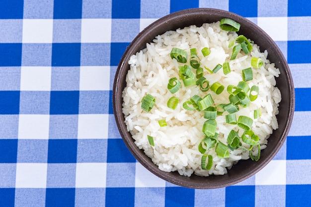 Kom witte rijst met groene ui op de lijst - typisch braziliaans voedsel