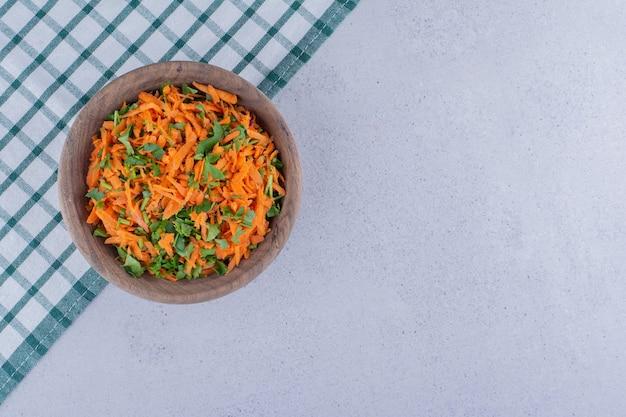 Kom wortelsalade op een tafelkleed op marmeren achtergrond.
