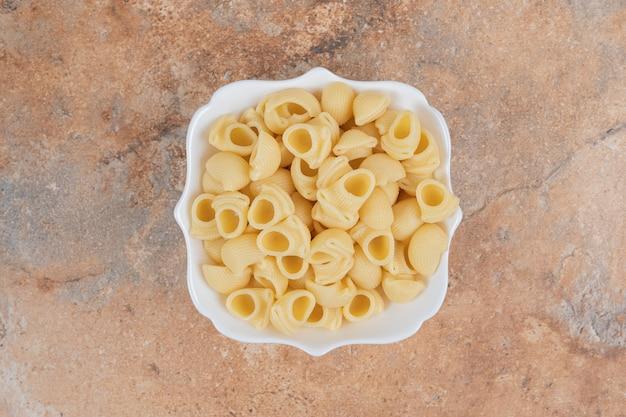 Kom zeeschelpvormige pasta op marmeren achtergrond