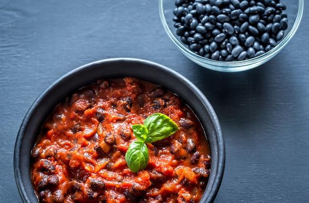 Kom zwarte bonen chili op zwarte tafel