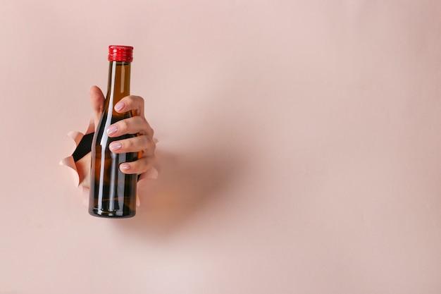 Kombucha-drankje in een fles in een vrouwelijke hand die door een rond gat in roze papier wordt gehouden