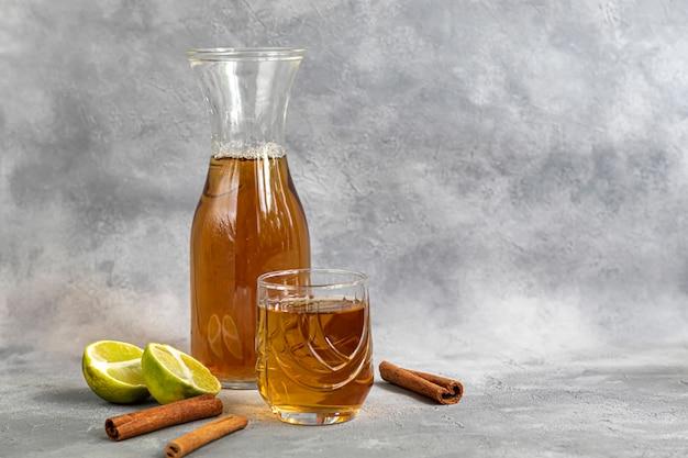 Kombucha of cider, gefermenteerde drank op een grijze achtergrond. een probiotische gezonde drank is kombucha.