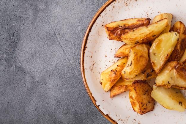 Komijn van gebakken aardappelpartjes. vegetarische aardappelpartjes. bovenaanzicht