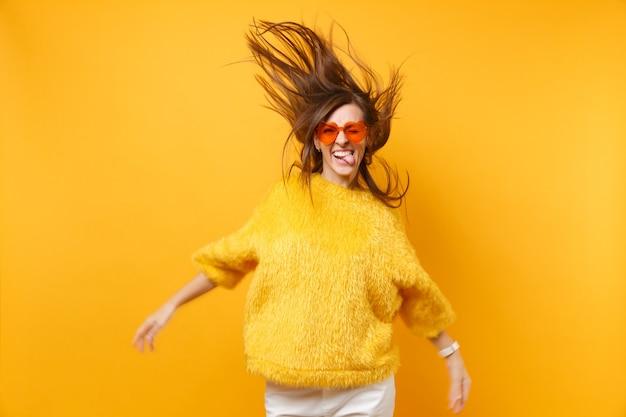 Komische jong meisje in bont trui hart oranje bril met tong, gek rond in studio sprong met vliegende haren geïsoleerd op gele achtergrond. mensen oprechte emoties, levensstijl. reclame gebied.