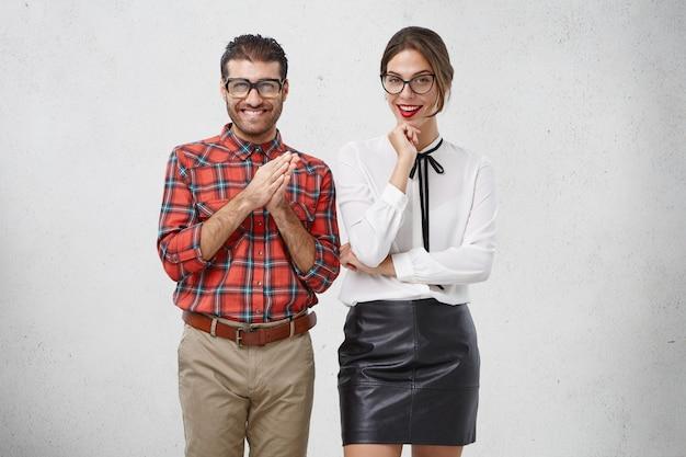 Komische jonge mannelijke wonk in formele kleding, heeft een intrigerende uitstraling, houdt de handpalmen bij elkaar