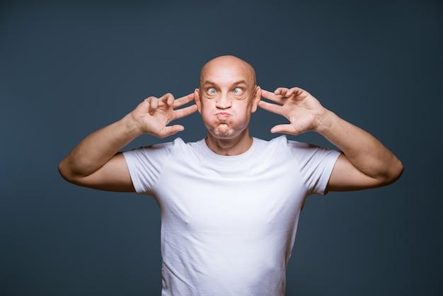 Komische kale man poseren op een blauwe muur met opgewonden gezichtsuitdrukkingen en opgeheven handen op zijn hoofd