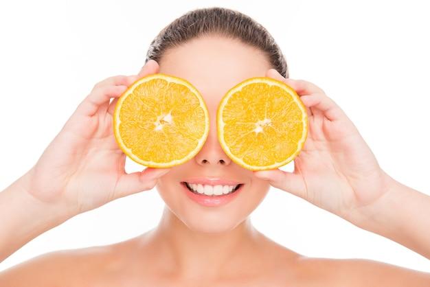 Komische lachende vrouw met twee helften van sinaasappel in de buurt van de ogen