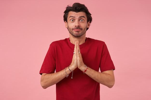 Komische opgewonden jongeman met stoppels in rode t-shirt grappig gezicht maken en houdt de handen in biddende positie