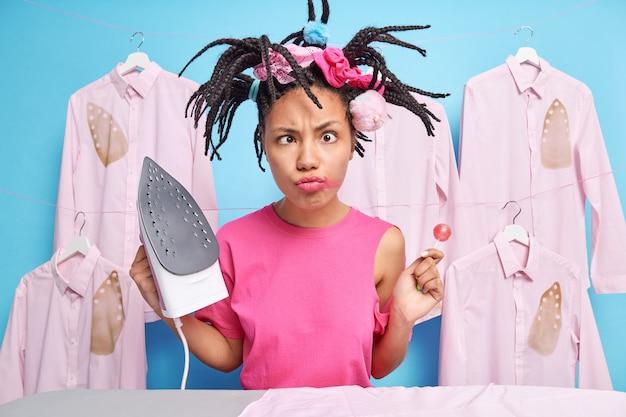 Komische vrouwelijke tiener kruist ogen en maakt een grappige grimas tijdens het strijken tegen verbrande gestreken shirts