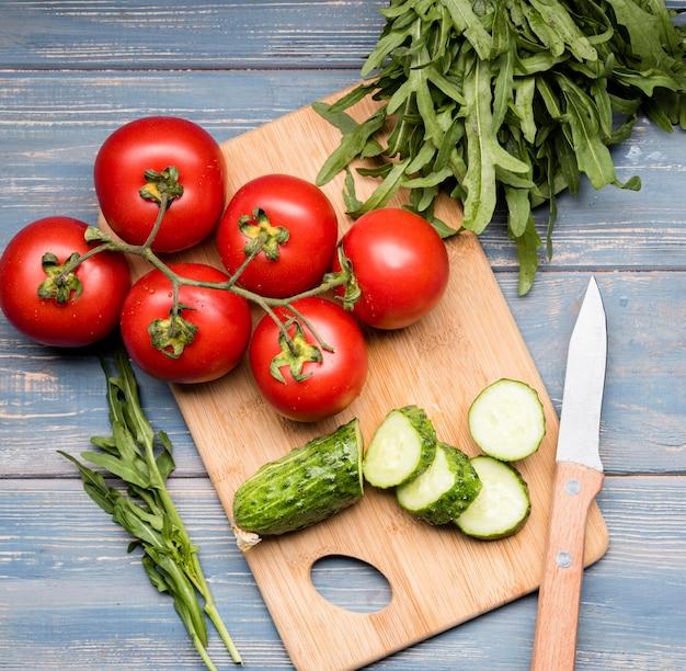 Komkommer en tomaten op snijplank