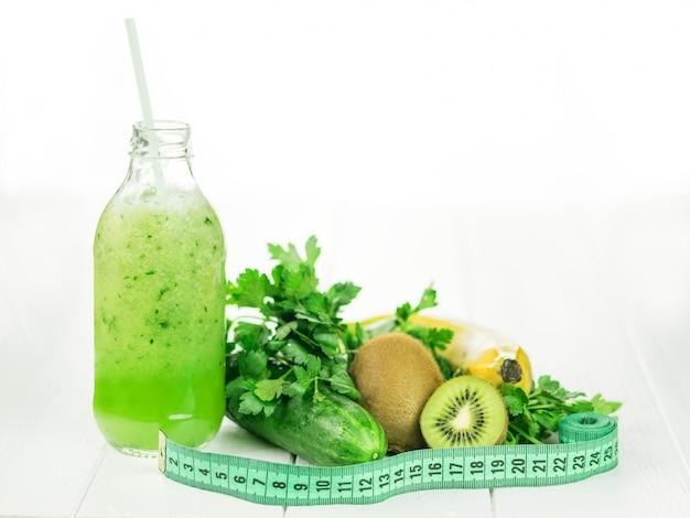 Komkommer, kiwi, banaan, peterselie en een fles smoothie op een witte houten tafel.