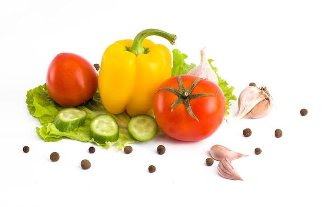 Komkommer met tomaat en peper op een witte achtergrond. groenten op een witte achtergrond. veelkleurige groenten op een witte achtergrond.