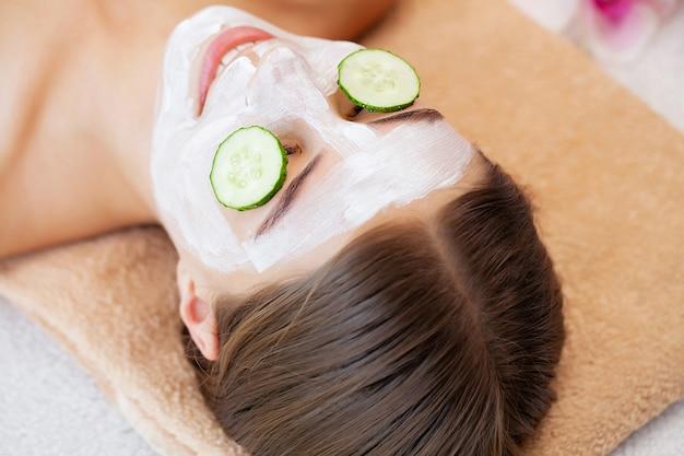 Komkommer over de ogen en een masker van witte klei voor gezichtsverzorging