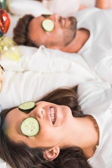 Komkommer plakjes over het gezicht van het stel op bed