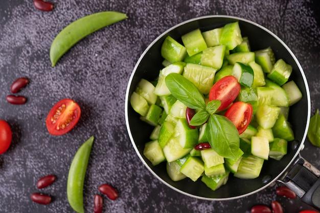 Komkommer roergebakken met tomaten en rode bonen in een koekenpan.