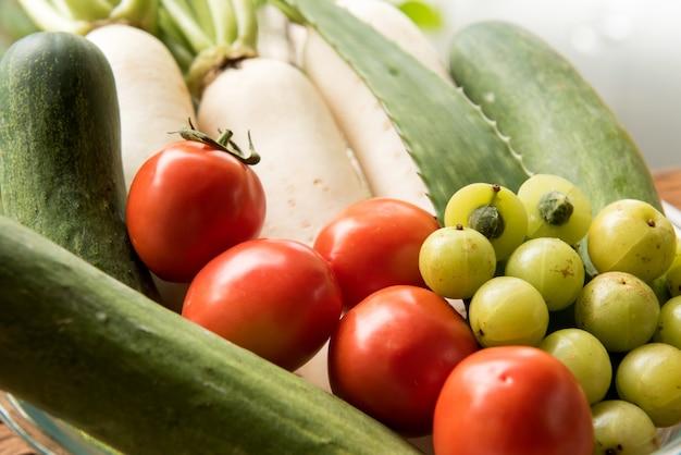 Komkommer, tomaat, radijs en indiase kruisbes op de achtergrond van de natuur.