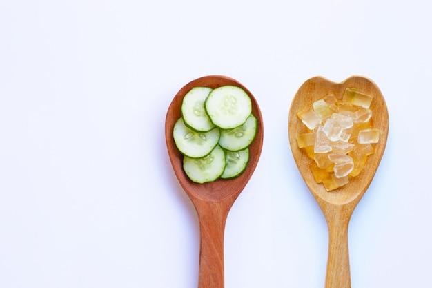 Komkommerplakken met het gel van aloëvera in houten lepel op wit