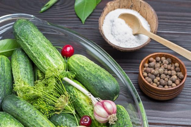 Komkommers en dille takjes, knoflook in glazen kom. zoete erwten en zout in kokosnootschil. zelfgemaakte fermentatieproducten