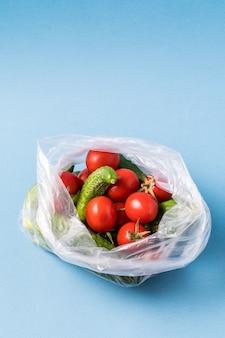 Komkommers en tomaten in plastic zak. stop met het gebruik van het concept van kunstmatige voedselzakken.