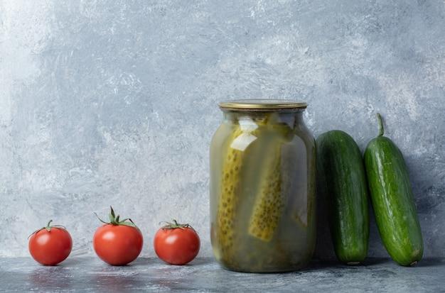 Komkommers gebeitst in een glazen pot op een marmeren achtergrond.