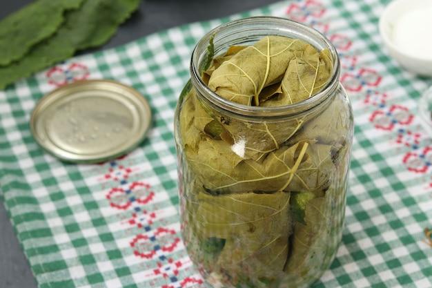 Komkommers in druivenbladeren worden in een pot met knoflook en dille gedaan om te beitsen, het voorbereidingsproces