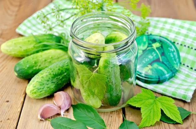 Komkommers in een glazen pot en op de tafel, knoflook, dragon, dille, bedek met servet, bladeren op de achtergrond van een houten planken