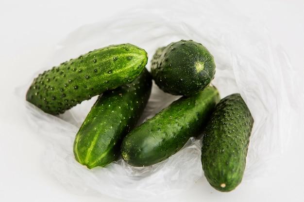 Komkommers in een plastic zak op een lichte achtergrond