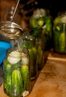 Komkommers in glazen potten vullen met kokend water voor conservering.