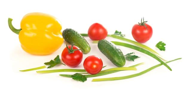 Komkommers, paprika's, tomaten en groene uien geïsoleerd op een witte ondergrond