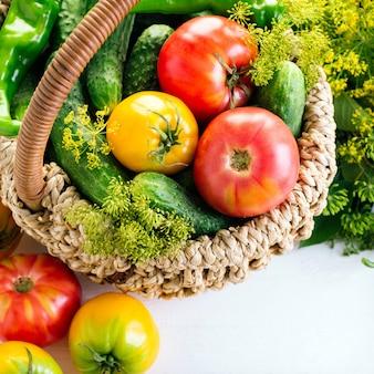 Komkommers, tomaten en dilleparaplu's in een mand
