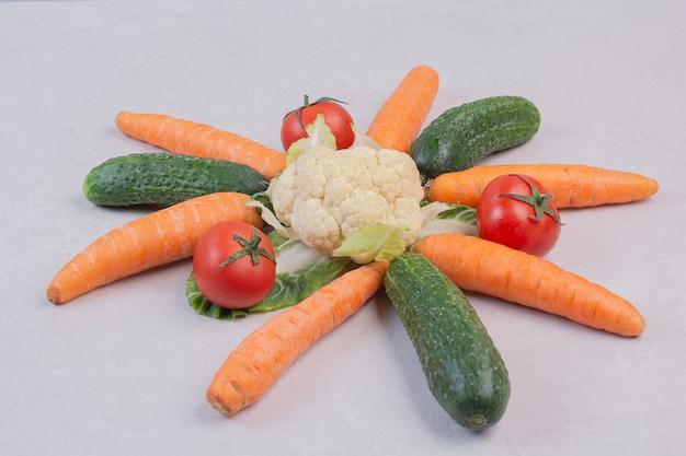 Komkommers, wortelen, bloemkool en tomaten op witte tafel.