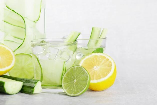 Komkommerwater in een fles en glas met limoen en citroen