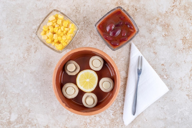 Kommen champignons, rode saus en maïskorrels op marmeren oppervlak