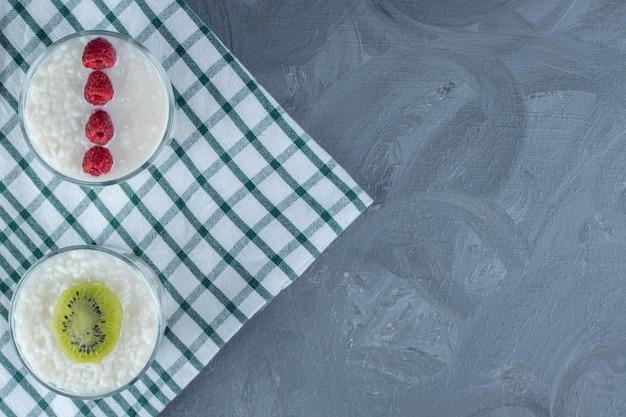 Kommen melkachtige rijst gegarneerd met frambozen en kiwiplak op een tafelkleed op marmeren achtergrond.
