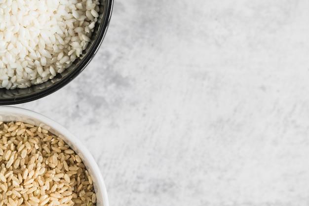 Kommen met bruine en witte rijst op tafel