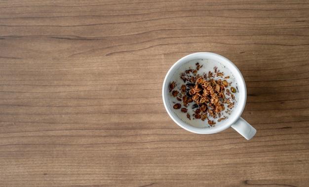 Kommen met chocoladecornflakes en melk voor ontbijt op houten lijst. bovenaanzicht