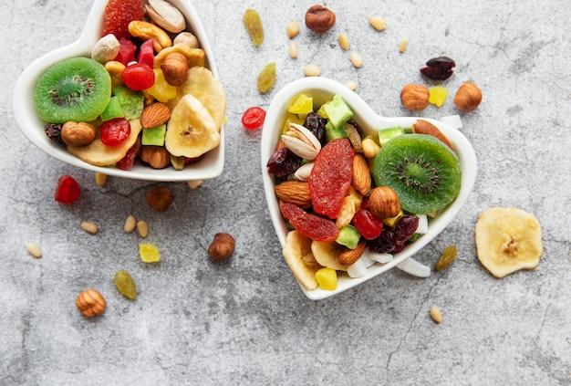 Kommen met diverse gedroogde vruchten en noten op een grijze betonnen ondergrond