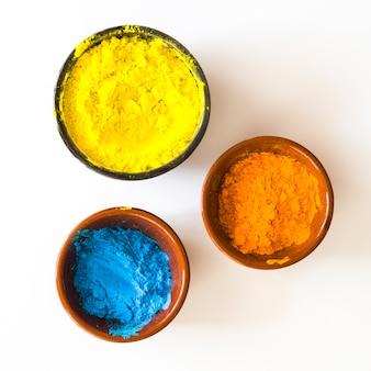 Kommen met geel; oranje en blauwe kleur poeder geïsoleerd op een witte achtergrond