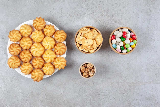 Kommen met geglazuurde pinda's, snoepjes en koekjeschips naast een bord koekjes op een marmeren oppervlak.